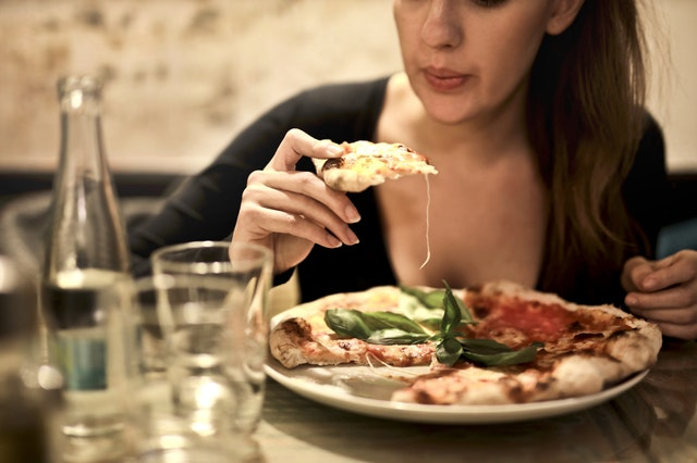 picture of woman eating neapolitan pizza